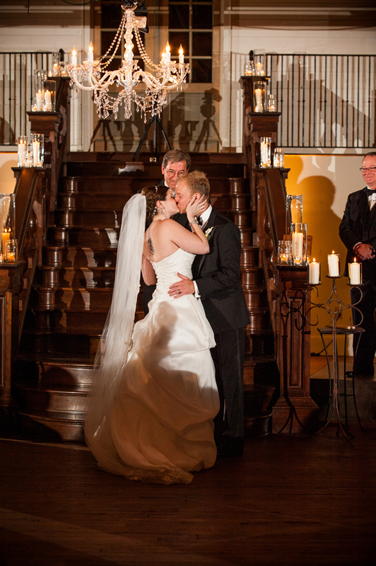 A couple takes vows by the grand staircase at Summerour Studio.